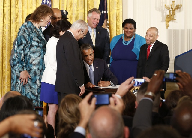 U.S. President Barack Obama signs an Executive Order to protect LGBT employees from workplace discrimination while at the White House in Washington